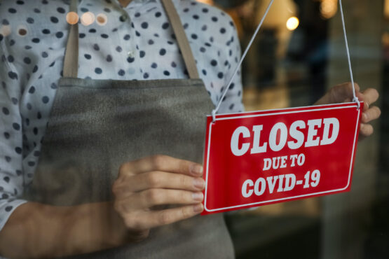 Woman in mask putting red sign with words Closed Due To Covid-19 hanging onto glass door, closeup